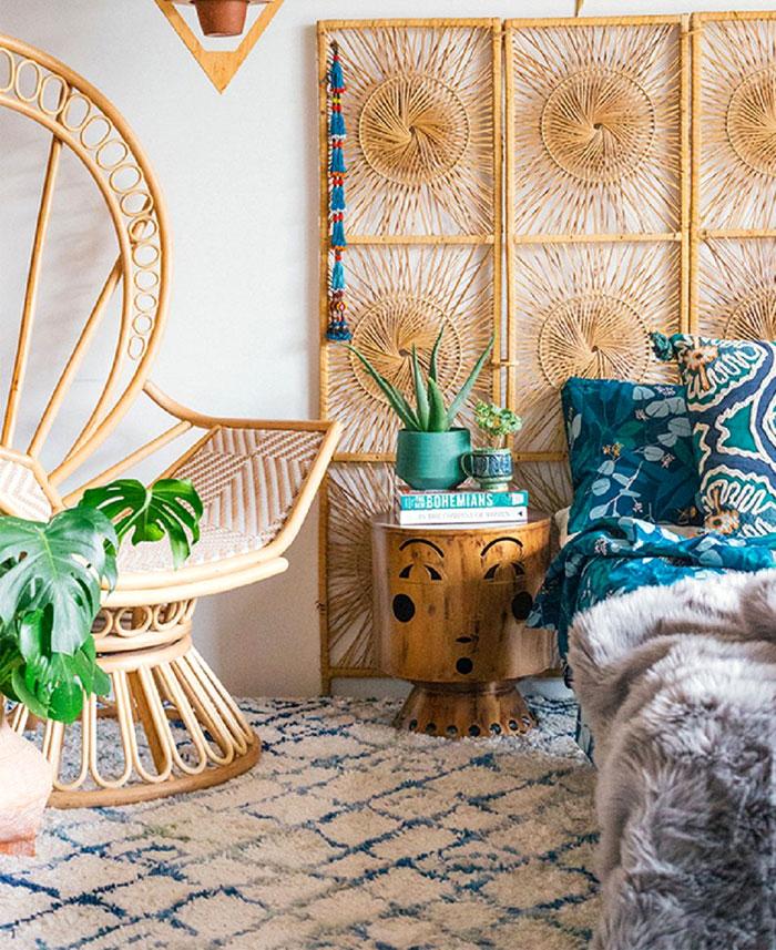 Habitación decorada al estilo boho chic con silla de pavo real y accesorios